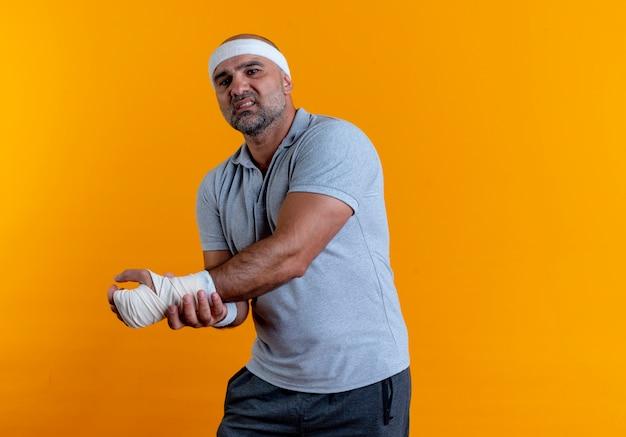 Reifer sportlicher mann im stirnband, der seine hand berührt, die unwohl sieht und schmerzen hat, die über der orangefarbenen wand stehen