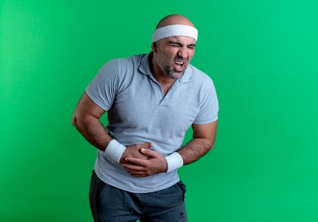 Reifer sportlicher mann im stirnband, der unwohl sieht und seinen bauch berührt, der unter schmerzen leidet, die über grüner wand stehen