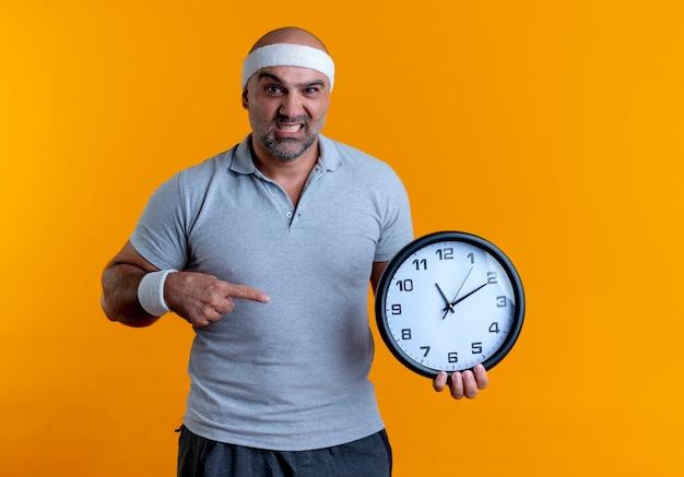 Reifer sportlicher mann im stirnband, der wanduhr hält, die mit dem finger darauf zeigt und nach vorne schaut, mit wütendem gesicht, das über orange wand steht