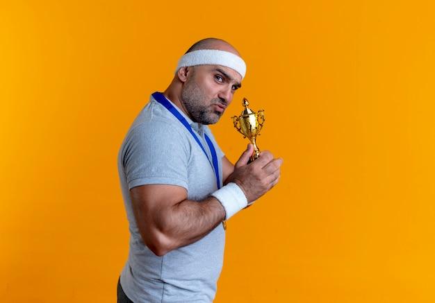 Reifer sportlicher mann im stirnband mit goldmedaille um den hals, der trophäe hält, die nach vorne mit ernstem gesicht steht, das über orange wand steht