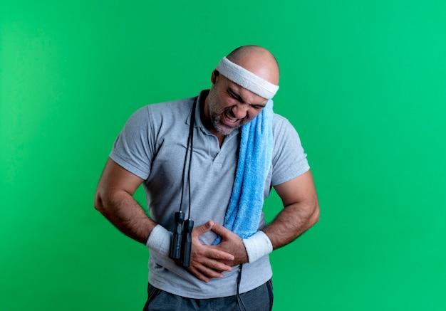 Reifer sportlicher mann im stirnband mit handtuch um den hals, das seinen bauch berührt, der unter schmerzen leidet, die über grüner wand stehen