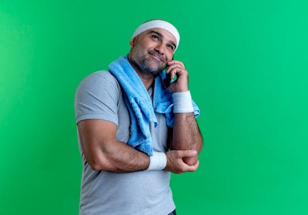 Reifer sportlicher mann im stirnband mit handtuch um den hals, der auf handy mit lächeln auf gesicht steht, das über grüner wand steht