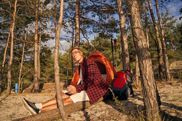 Reifer sportlicher mann sitzt im holz mit ausrüstung für nordic walking und macht sich notizen im skizzenbuch