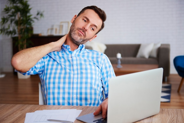 Reifer unternehmer mit nackenschmerzen