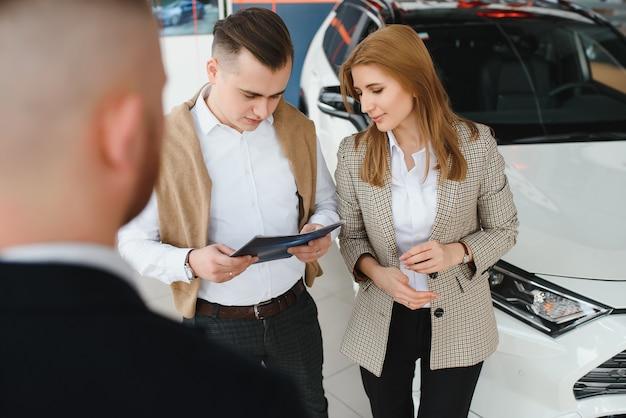 Reifer verkäufer, der einem paar im ausstellungsraum neues auto zeigt