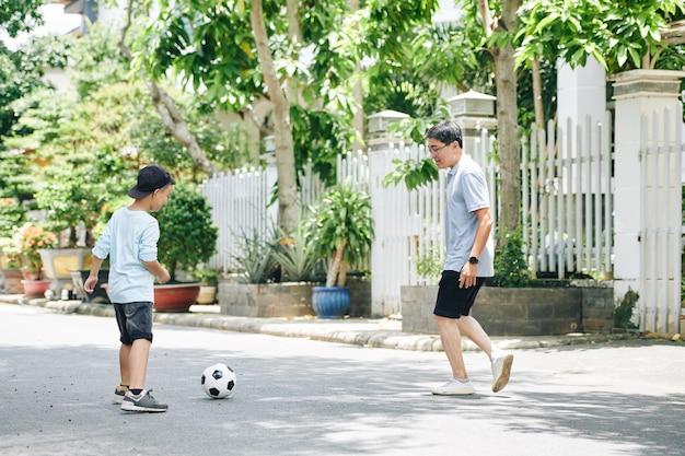 Reifer vietnamesischer mann, der fußball mit jugendlichem sohn auf der straße spielt
