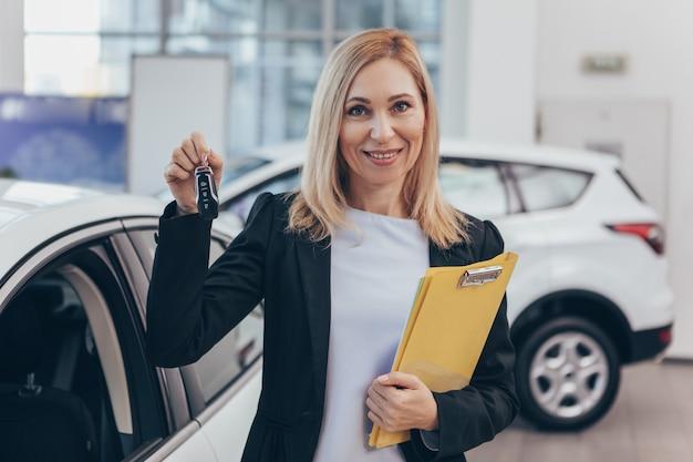 Reifer weiblicher autohändler, der zur kamera hält die autoschlüssel stehen vor einem neuen automobil lächelt
