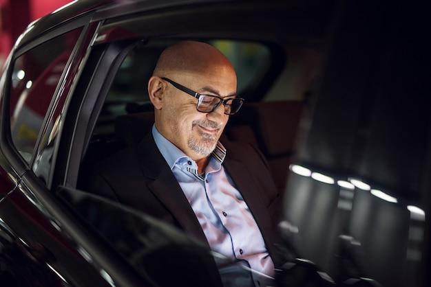 Reifer zufriedener geschäftsmann schaut auf seinen laptop, während er auf einem rücksitz in einem auto fährt.