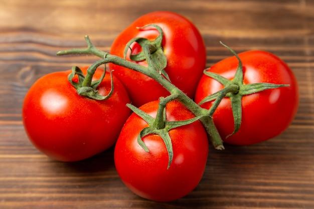 Reifes gemüse der roten tomaten der vorderansicht auf rotem reifem frischem diät-salat des braunen schreibtisches