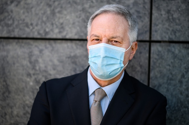 Reifes geschäftsmannporträt im freien, das eine schutzmaske gegen covid 19 coronavirus-pandemie trägt