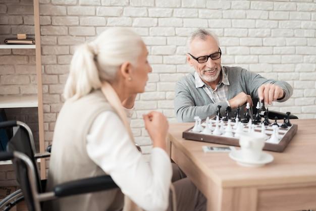 Reifes glückliches paar im rollstuhl spielen schach.