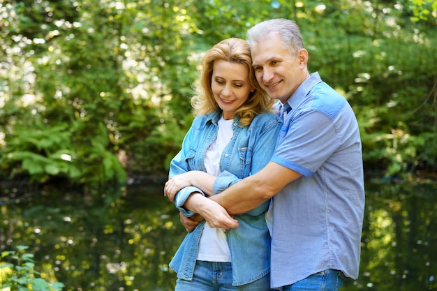 Reifes glückliches paar steht an einem sonnigen tag im wald und umarmt. das konzept glücklicher familiärer beziehungen