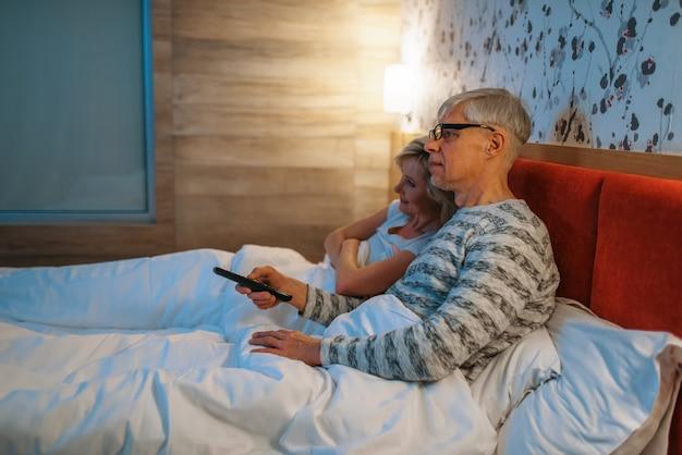 Reifes liebespaar beim fernsehen im schlafzimmer