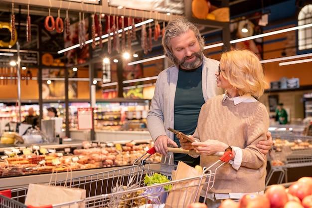 Reifes liebevolles paar, das bespricht, was man im supermarkt kauft, während man entlang einer der anzeigen geht und wagen mit nahrungsmitteln schiebt