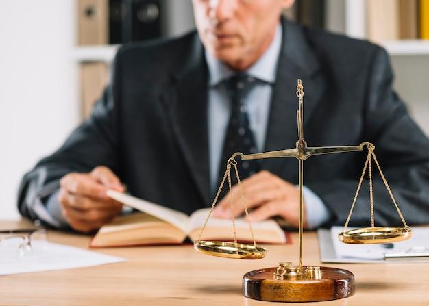 Reifes männliches rechtsanwaltlesebuch mit gerechtigkeitsskala über dem schreibtisch