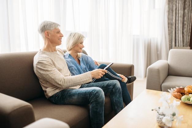 Reifes paar, das auf der couch sitzt und fernsieht, glückliche familie. erwachsener ehemann und ehefrau, die zu hause ruhen