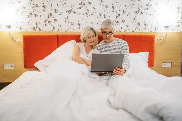 Reifes paar, das auf laptop im schlafzimmer vor dem schlafengehen schaut. mann in brille und frau im bett liegend