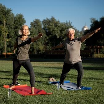Reifes paar, das draußen yoga macht