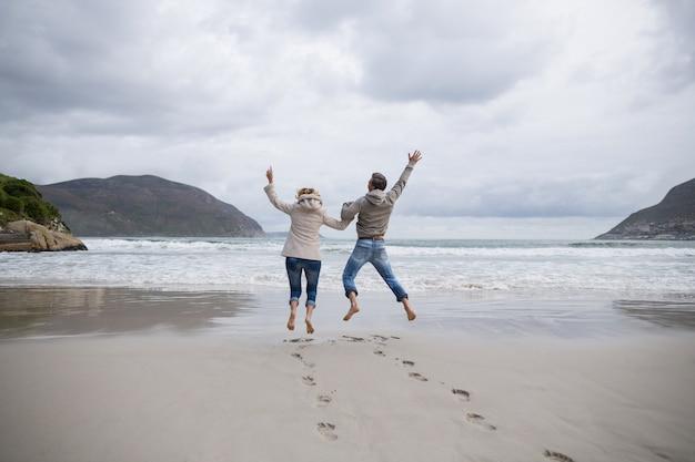 Reifes paar, das in luft am strand springt