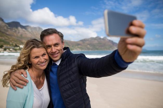 Reifes paar, das selfie mit handy nimmt