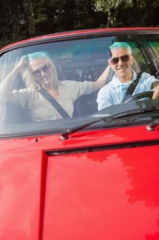 Reifes paar im roten cabriolet, der an der kamera lächelt