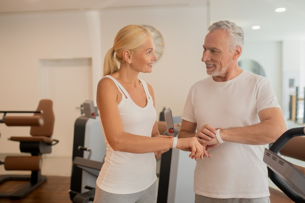 Reifes paar prüft pulsometer im fitnessstudio und sieht positiv aus