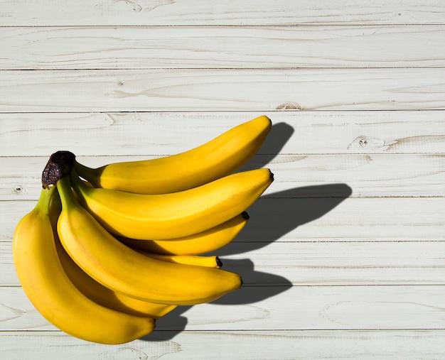 Reifes süßes gelbes bananenbündel auf tisch