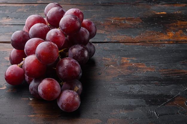 Reifes traubenset, dunkelrote früchte, auf altem dunklem holztisch
