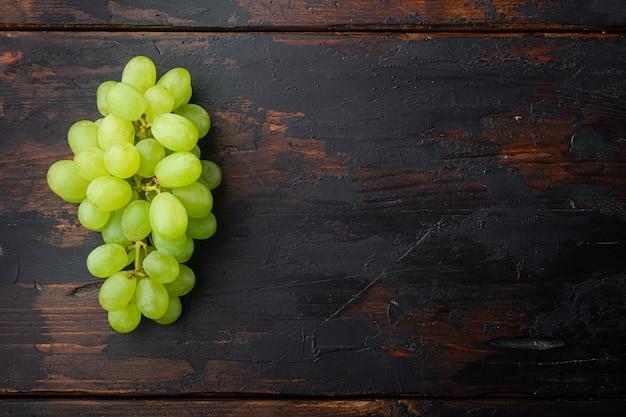 Reifes traubenset, grüne früchte, auf altem dunklem holztisch, draufsicht flach legen