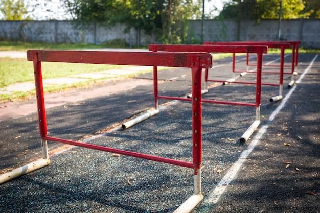Reihe alter roter hürden für ein hürdenrennen auf einem verlassenen stadion