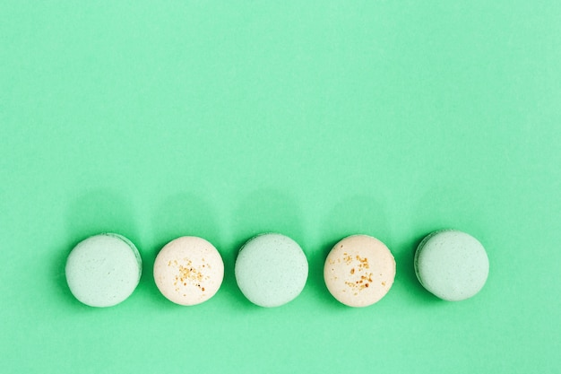 Reihe aus süßen makronen sortiert lecker und in verschiedenen farben. runde kekse auf farbtrendminze. süßes essen und gesundheitsschädlich.