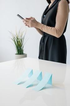 Reihe der blauen papierkarten auf schreibtisch auf hintergrund der geschäftsfrau, die im smartphone im büro rollt