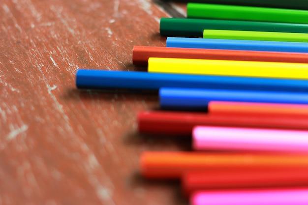 Reihe der bleistiftfarbe (nicht benutzt) mit buntem ton auf hölzerner tabelle