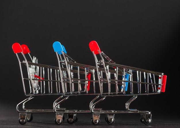Reihe der einkaufswagen mit den roten und blauen griffen