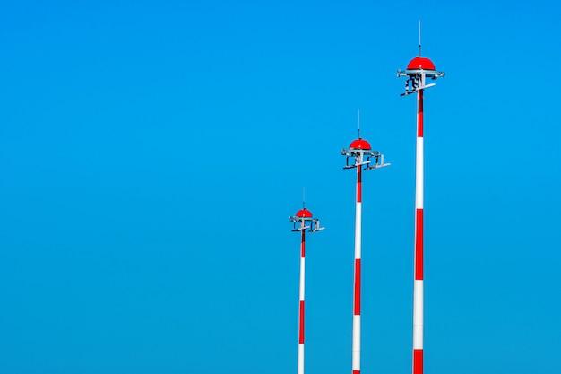 Reihe der flughafenlaternenpfosten mit abwechselndem rotem und weißem gemälde auf blauem himmel