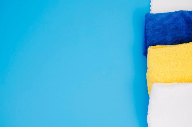 Reihe der gefalteten bunten weichen serviette gegen blauen hintergrund