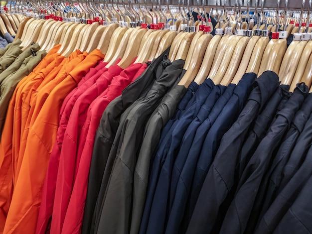Reihe der hellen jackenkleidung auf aufhänger im shop