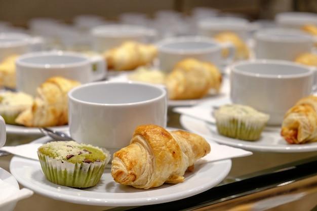 Reihe der kaffeetasse und des kleinen kuchens, hörnchen stellte für break-seminar oder das treffen ein