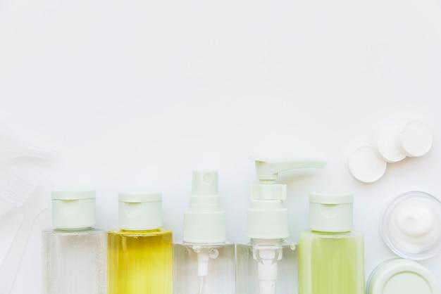Reihe der kosmetischen sprühflasche mit geschlossenem deckel und feuchtigkeitscreme gegen weißen hintergrund