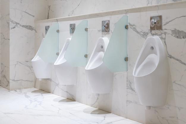 Reihe der öffentlichen toilette der toilettenmänner, weiße urinale der nahaufnahme im badezimmer der männer