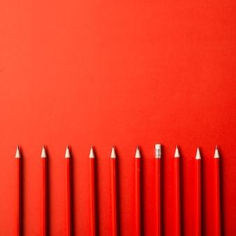 Reihe der roten scharfen bleistifte auf rotem hintergrund