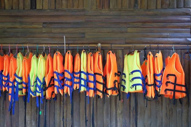 Reihe der schwimmweste, die für touristische dienstleistungen hängt.