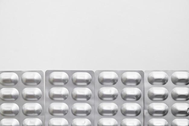 Reihe der silbernen blisterpackungspillen lokalisiert auf weißem hintergrund