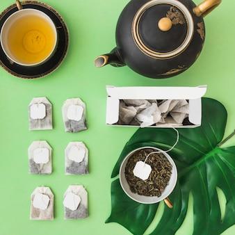 Reihe der verschiedenen teebeutel mit teeschale und teekanne auf blassem grünem hintergrund