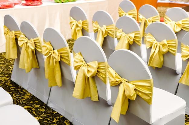 Reihe der weißen stühle verziert mit goldbändern