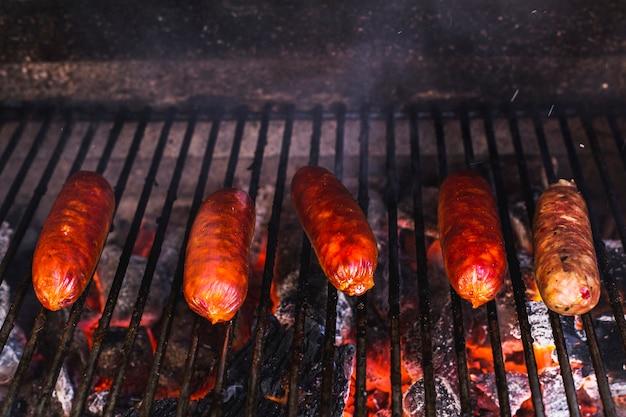 Reihe der würste, die über kohlen im grill gekocht werden