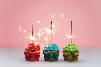 Reihe des belichteten Feuerwerks über den kleinen Kuchen gegen rosa Hintergrund