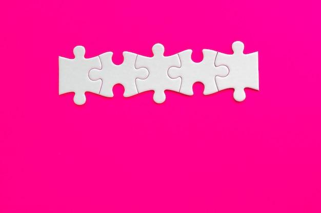 Reihe des weißen puzzles auf fuchsia hintergrund