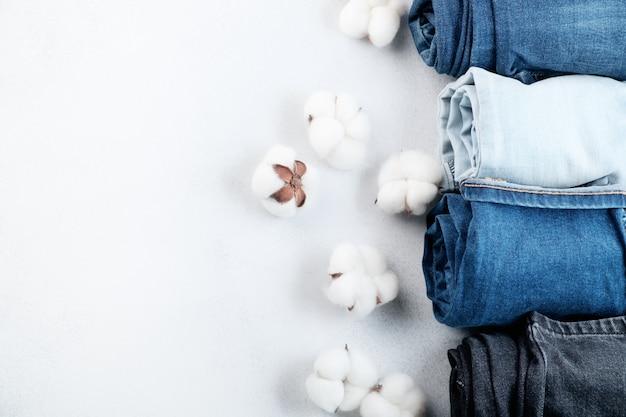 Reihe gerollter jeans und baumwollblumen auf hellem hintergrund