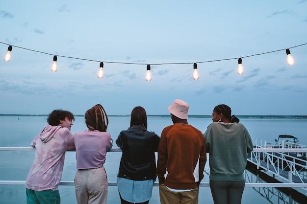 Reihe junger erholsamer freunde, die auf pier stehen